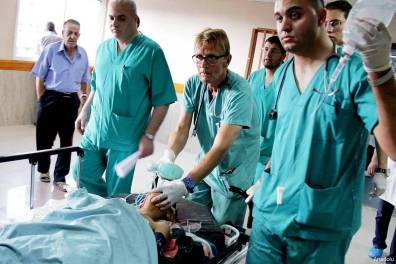 Dr Mads Frederick Gilbert (centre) at Al-Shifa hospital on July 17th, treating a wounded Palestinian child, after an Israeli air strike killed 4 children and wounded 5 others. (Photo: MEMO)